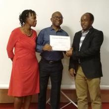 Mr Damaseke Chibale receiving his certificate of completion from the Deputy Executive Director, IUCEA, Prof. Mike Kuria and supported by IUCEA Communication Officer, Ms Agnes Assimwe.