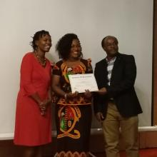 Mrs Patricia Sakala receiving his certificate of completion from the Deputy Executive Director, IUCEA, Prof. Mike Kuria and supported by IUCEA Communication Officer, Ms. Agnes Assimwe.